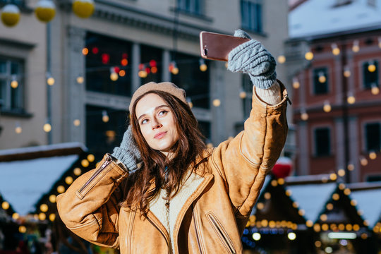 Young stylish intelligent woman making selfie on christmas market, smiling happy.