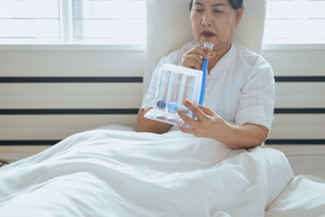 Patient elderly people woman using incentive spirometer or three balls for stimulate lung in bedroom