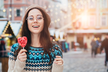 Sweet, chill, emotions and inspiration concept - positive portrait of stylish intelligent woman with candy on the old town square with the Christmas market i in the winter, Europe. Sun glare effect
