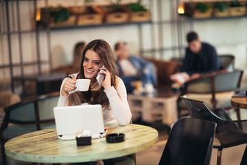Young woman sitting in front of open laptop computer in cafe bar using phone