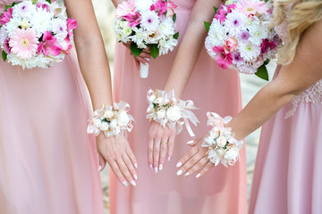 Glorious bridesmaids in pink dresses holding beautiful flowers - selective focus