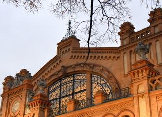 Beleuchtete Fassade der Hala Gwardii mit Ästen im Vordergrund