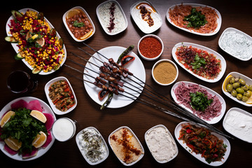 Traditional Turkish liver shish kebab plate on wooden table with cumin powder, pepper flakes, sauces, appetizers, mezes and salads.