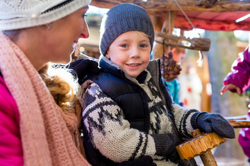 Mother with son and carousel on traditional Christmas market