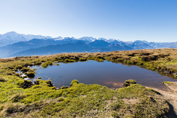 Autumn landscape on the Niederhorn with a pond in the foreground and the Alps in the background on a beautiful autumn day in Switzerland
