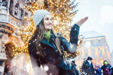 Woman enjoying Christmas time in the city while it is snowing