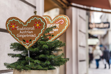 Vienna, Austria - December 30, 2017. Gingerbread bakery signs with traditional cookies in heart shape and text. Close view of plate with ornament and christmas tree branches.