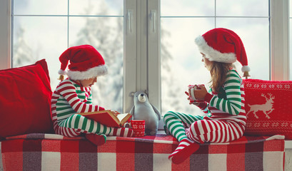 children girl and boy is sad on Christmas morning by the window.