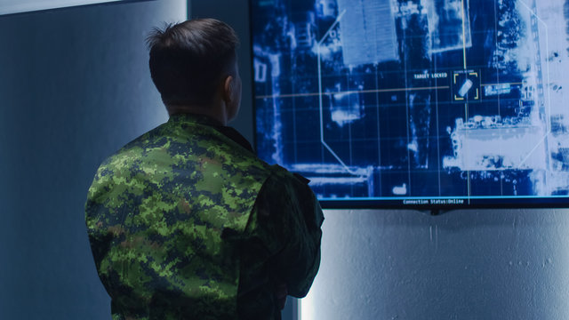 Military Man / Army Officer Watches Satellite Surveillance Footage / Car Tracking of the Target on Wall TV Screen. Secret Military Spying Operation in the Surveillance Center / System Control Room.