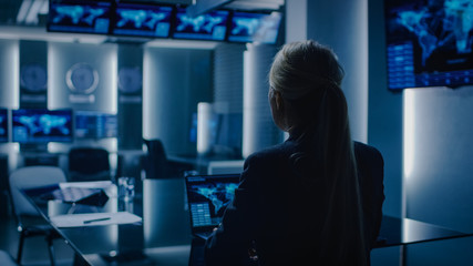 Female Special Agent Works on a Laptop in the Background Special Agent in Charge Talks To Military Man in Monitoring Room. In the Background Busy System Control Center with Monitors Showing Data Flow.