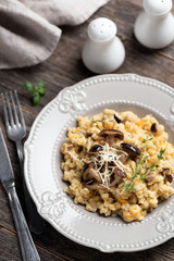 Barley mushroom risotto on plate. Traditional italian cuisine meal, vegetarian risotto with pearl barley and mushrooms on rustic wooden table, top view