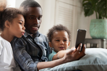 Happy African American family using mobile phone together, father with daughter and son make selfie photo, watching video, sitting on couch at sitting room, making video call, using mobile application