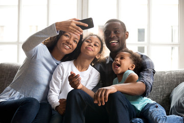 Happy African American large family taking selfie on phone together, attractive mother holding smartphone phone, taking family photo, smiling father, little preschooler daughter and toddler son posing