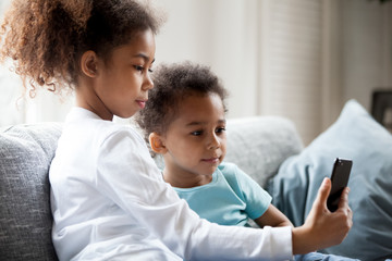 Pretty African American children using smartphone at home, little preschooler girl sitting together on couch with toddler boy holding phone in hands, taking photo, making selfie, watching video