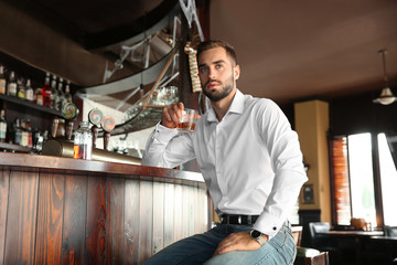 Young man drinking whiskey in pub