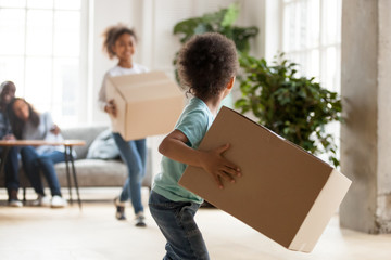 Happy African American family moving in new house, toddler boy carrying cardboard box, playing with preschooler sister, mother and father sitting on couch, looking at children, rear view, close up Wall mural