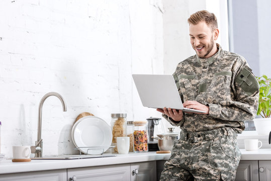 handsome army soldier in uniform using laptop at kitchen