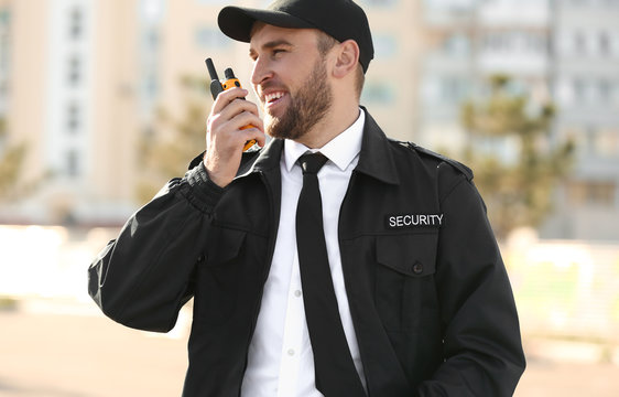 Male security guard with portable radio transmitter outdoors