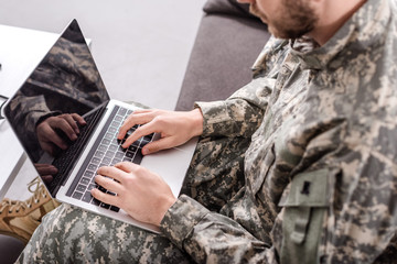 partial view of army soldier using laptop on couch