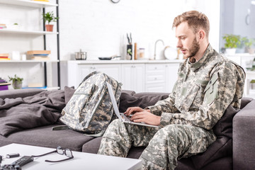 focused army soldier using laptop on couch at home