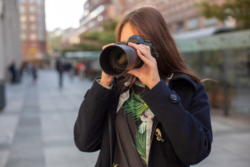 Attractive tourist woman photographer with camera, outdoor in city street.