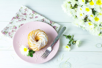 Delicious cakes with coconut chips on pink plate on white table