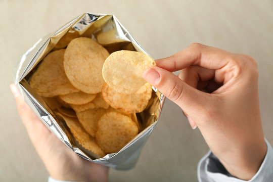 Woman eating tasty potato chips, closeup
