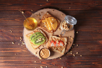 Board with different delicious toasts and honey on wooden table