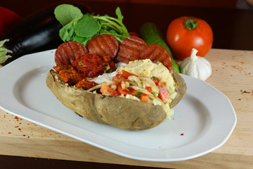 Kumpir - Traditional Turkish meal with baked potato, butter, cheese, bulgur salad, beef sausage and hot spices