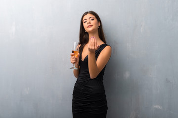Teenager girl with champagne celebrating new year 2019 presenting and inviting to come