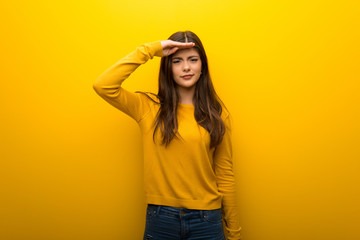 Teenager girl on vibrant yellow background looking far away with hand to look something Wall mural