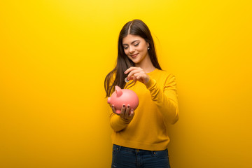Teenager girl on vibrant yellow background taking a piggy bank and happy because it is full