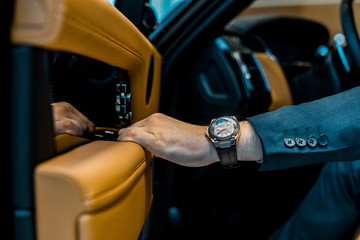 cropped image of businessman with luxury watch closing door while sitting in car
