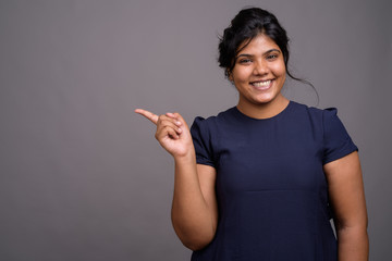 Young overweight beautiful Indian woman against gray background