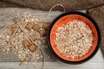 Different cereals in a plate on a gray wooden background. View from above.