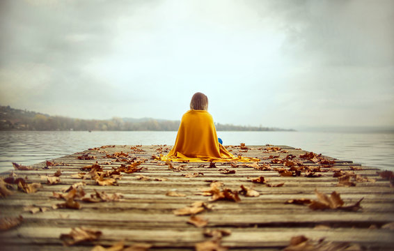 Girl sitting on a pier, looking the horizon