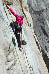 A girl climber climbs the rock wall. Competitions in rock climbing.
