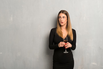 Woman with champagne celebrating new year 2019 having doubts and with confuse face expression