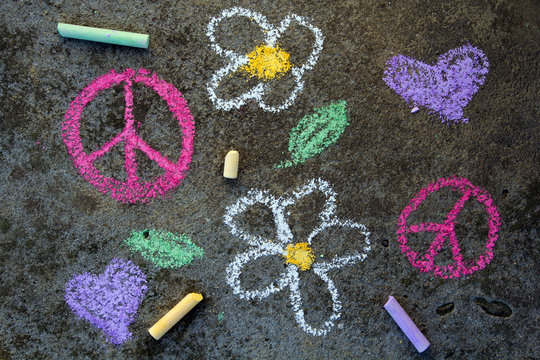 Colorful chalk drawing on sidewalk: Pink peace symbol and beautiful flowers