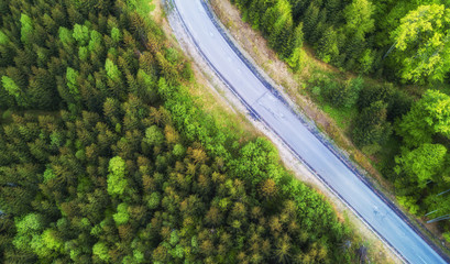 Aerial view on the road in summer forest. Beautiful natural landscape from air. Green forest and road as a background from drone.