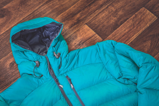 Close up detail shot of a down jacket on wood background. Winter sports jacket on wooden floor.