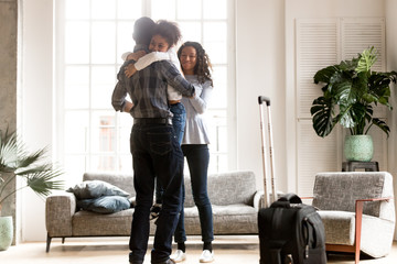 Happy African American family together in living room, loving father holding little preschooler daughter in hands, embracing, smiling attractive wife greeting husband after business trip, journey