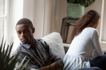Offended African American couple sitting separately after quarrel on couch at home, not talking, ignore each other, misunderstanding, man and woman having relation problems, difficulties, break up