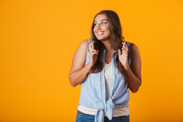 Happy young woman posing isolated over yellow wall background showing hopeful gesture.