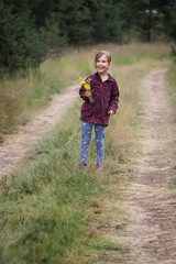 Lovely little girl walking along a forest path