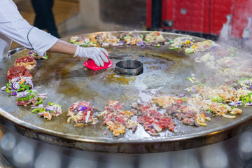 Cooking street food on a large firebox. Frying meat and seafood on the brazier in the street