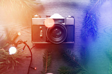 Top View of Vintage Camera Between Christmas decorations, Christmas tree, warm and cold toning, lights, garlands, bokeh on Wooden Texture