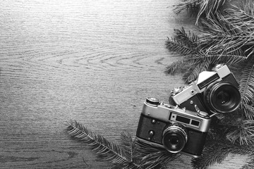 Top View of Vintage Camera Between Christmas tree, on Wooden Texture, copy space, black and white