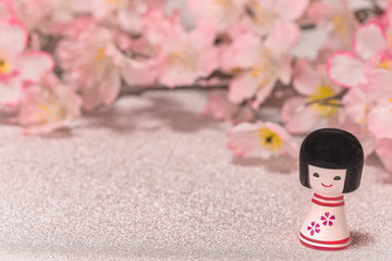 Japanese New Year's Cards with little doll Kokeshi with flower pattern on a glitter silver background with a branch of cherry blossoms flowers.