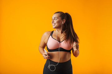 c5689c7195 Portrait of sporty chubby woman in sportive bra listening to music with  earphones and smartphone